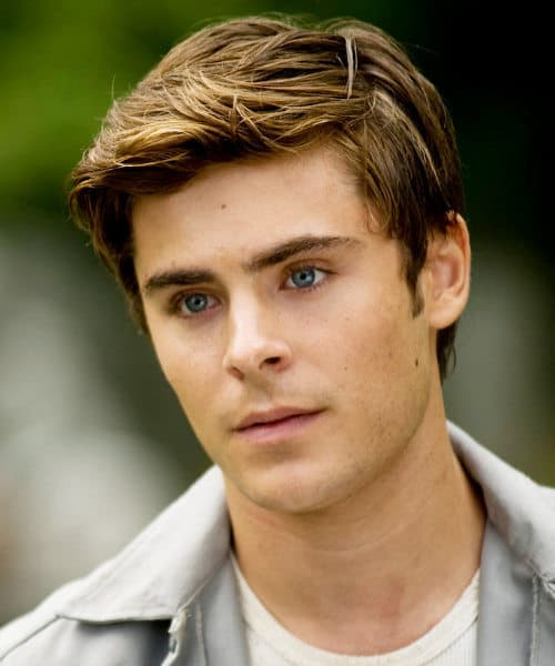Photo of Zac Efron side parted hairstyle.